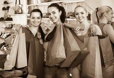 选择鞋子的三名妇女在商店 图库摄影