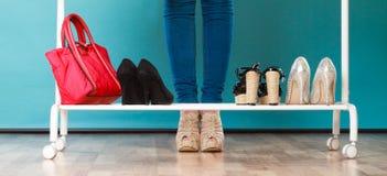 选择鞋子的妇女佩带在购物中心或衣橱 免版税库存照片