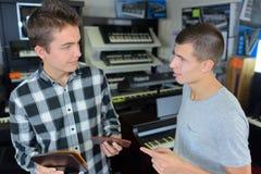 选择音乐的年轻人在音乐商店 图库摄影