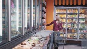选择食物的成熟妇女在超级市场在房子附近 股票录像