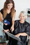 选择头发颜色的客户和美发师 免版税库存图片