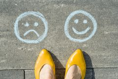 选择-愉快面带笑容或不快乐,在柏油路的文本 免版税库存照片