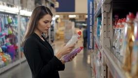 选择洗涤剂的妇女在杂货店 女实业家在超级市场 库存照片