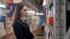 选择洗涤剂的妇女在杂货店 女实业家在超级市场 库存图片