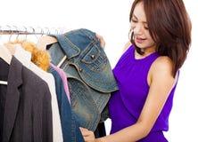 选择购物衣裳的愉快的微笑的亚裔妇女 免版税库存照片