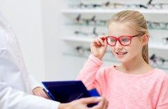 选择玻璃的眼镜师和女孩在光学商店 免版税库存图片