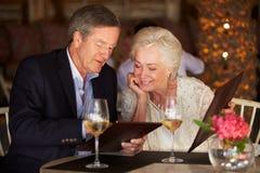 选择从菜单的资深夫妇在餐馆 免版税库存照片
