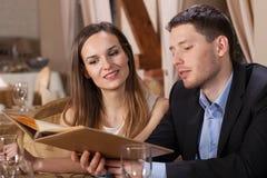 选择从菜单的年轻夫妇 库存图片