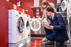 选择洗衣机的夫妇在大型超级市场 免版税库存图片