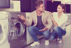 选择洗衣机的年轻快乐的夫妇在大型超级市场 免版税库存图片