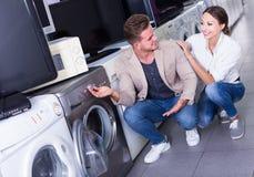 选择洗衣机的年轻正面夫妇在大型超级市场 免版税图库摄影