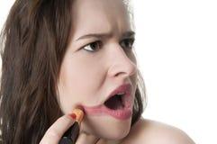 透支她的唇膏的少妇在她的嘴唇外面。 库存照片
