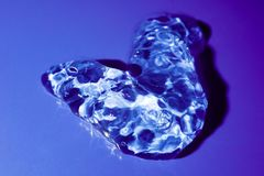 透明发光的胶凝体下落在紫罗兰色背景宏指令的 图库摄影
