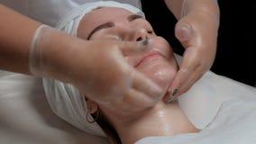 透明手套的美容师分布在客户` s面孔的前额、面颊和下巴的奶油 美好的w 股票视频