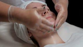 透明手套的美容师分布客户` s面孔的脖子、面颊和下巴的奶油 A 股票录像