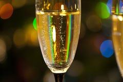 透明杯与泡影的香槟在闪亮金属片或衣服饰物之小金属片背景中  图库摄影