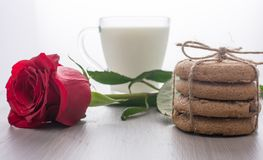 透明杯子牛奶,堆曲奇饼, perevyazanaya麻线,在一朵红色玫瑰旁边说谎 被弄脏的背景, bokeh 免版税库存照片
