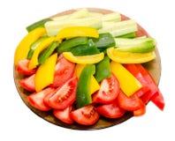 透明板材用切的红色蕃茄、黄色和绿色辣椒的果实和黄瓜 免版税库存图片