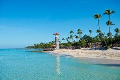 透明海水和清楚的天空 在一个含沙热带海岛上的灯塔有棕榈树的 免版税库存图片