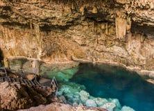 透明的水美丽的自然水池在与石笋和石笋的一个岩石洞形成了 库存照片