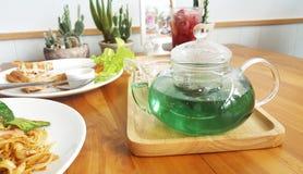 透明的茶罐用绿色蝴蝶豌豆茶和柠檬水 免版税图库摄影
