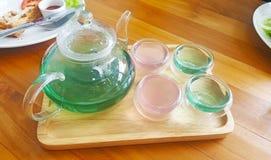 透明的茶罐用绿色蝴蝶豌豆茶和柠檬水 免版税库存图片