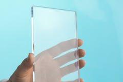 透明空白的未来微型计算机片剂在手中打电话 免版税库存图片