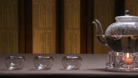 透明茶壶水壶的美好的温暖的图片用在一张桌上的鲜美绿色红茶与蜡烛 玻璃水壶 免版税库存照片