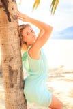 透明连衣裙的白肤金发的女孩在棕榈树干倾斜 免版税库存图片