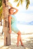 透明连衣裙的白肤金发的女孩在棕榈树干倾斜 免版税库存照片