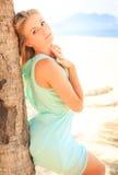 透明连衣裙的白肤金发的女孩在棕榈树干倾斜 图库摄影