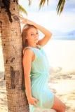 透明连衣裙的白肤金发的女孩在棕榈树干倾斜 库存照片