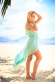 透明连衣裙的白肤金发的女孩在海滩的棕榈阴影 免版税库存照片