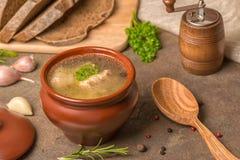 透明鱼汤用鲟鱼,在泥罐,装饰的土豆 免版税库存照片