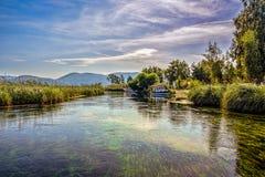透明,象水小河的水族馆在与疏散云彩的蓝天下 免版税库存照片