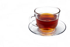 透明玻璃杯子用在被隔绝的茶碟的茶 免版税库存照片