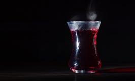 透明玻璃杯子用热的木槿茶 从上面的蒸气 黑色背景 库存照片