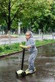 透湿在雨中,体育衣服的一个男孩在滑行车滑冰 春天步行在城市公园,多雨天气 免版税库存照片