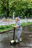 透湿在雨中,体育衣服的一个男孩在滑行车滑冰 春天步行在城市公园,多雨天气 免版税库存图片