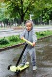 透湿在雨中,体育衣服的一个男孩在滑行车滑冰 春天步行在城市公园,多雨天气 免版税图库摄影