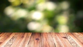 透视木头和bokeh轻的背景 产品显示模板 在迷离移动的自然绿色叶子的木台式 库存照片