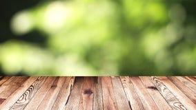 透视木头和bokeh轻的背景 产品显示模板 在迷离移动的自然绿色叶子的木台式 免版税库存照片