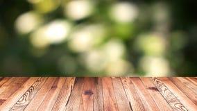 透视木头和bokeh轻的背景 产品显示模板 在迷离移动的自然绿色叶子的木台式 库存图片