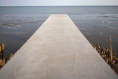透视长的水泥桥梁延伸到有自然s的海 免版税库存图片