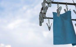 透镜在白色钳位的清洁布吊在洗涤以后 免版税图库摄影