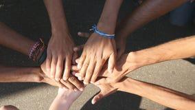 逐个一起堆积在团结和配合然后被举的所有种族和颜色的胳膊 许多多种族手 免版税库存照片