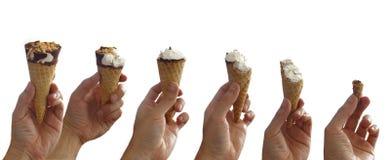 逐步被吃的冰淇凌的序列 供以人员拿着一个涂了巧克力的香草冰淇淋锥体用花生的` s手 免版税库存照片