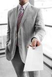 递一个邮寄的信封的商人 免版税库存照片