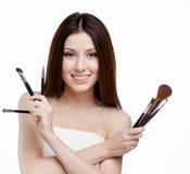 递一套化妆刷子的妇女 免版税库存照片