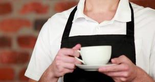 递一杯咖啡的微笑的barista 股票录像